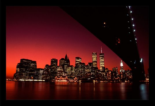 ©Mark D Phillips; This photograph featuring a blazing red sky over lower Manhattan was taken at one of my favorite spots in the 90s, at the Brooklyn anchorage of the Brooklyn Bridge.