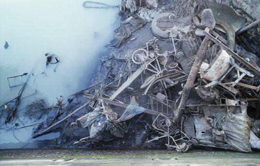 Low tide reveals metal garbage and milky water