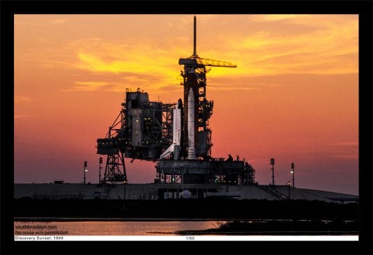 13 x 19 Framed Print, ©Mark D Phillips; the Space Shuttle Discovery on Pad 39 at Kennedy Space Center the night before its launch with a blazing sunset.