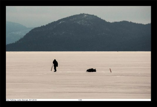 Ice fisherman on Lake George, New York, on a sea of ice in the Adirondacks.