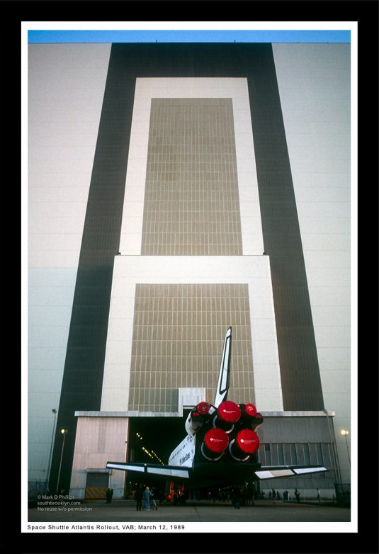 13 x 19 Framed Print, ©Mark D Phillips; The Space Shuttle Atlantis is dwarfed by the massive VAB (vehicle assembly building), March 12, 1989.